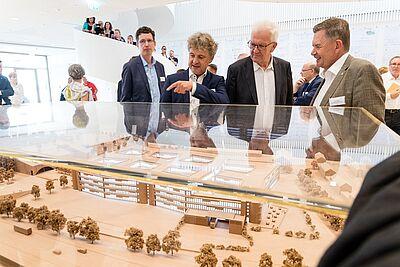 (v.r.) Erich Harsch, Vorsitzender der Geschäftsführung von dm, zusammen mit Ministerpräsident Winfried Kretschmann und Oberbürgermeister Dr. Frank Mentrup vor dem Modell der neuen Firmenzentrale. Foto: cg