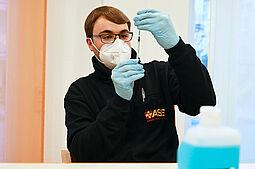 Helfer Sebastian Ohneseit (ASB) zieht den Impfstoff in eine Spritze auf. Foto: Benjamin Becker