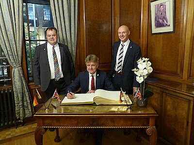 Oberbürgermeister Dr. Frank Mentrup trägt sich in das Goldene Buch der Stadt Nottingham ein. Councillor David Mellen (l.), Chief Executive Ian Curryer (r.). Foto: Stadt Karlsruhe