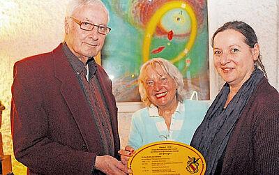 Amulett/Schild-Übergabe (v.l.): Wolfgang Schön, Initiatorin Gerda Schneider und Künstlerin Karin Münch. Foto: Volker Knopf/wobla