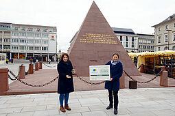 Bürgermeisterin Bettina Lisbach und Antonia Müller vom Umwelt- und Arbeitsschutz freuen sich über die Auszeichnung für das Saatgut-Projekt der Stadt. Foto: Stadt Karlsruhe