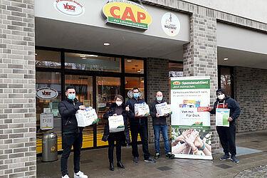 """Die Leiter der drei Karlsruher CAP-Märkte übergaben knapp 300 Spendentüten an Serdar Kunduz (rechts) und Sandra Czepielewski (2. v. links), den Gründern der Initiative """"Sei Mensch"""". Foto: Lebenshilfe Karlsruhe"""