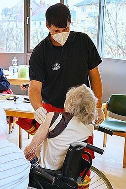 Helfer Jürgen Meger (DLRG) kümmert sich um die Einstichstelle einer geimpften Heimbewohnerin. Foto: Benjamin Becker