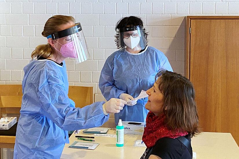 Dr. med. Wibke Hoffmanns (links) und Carola Naskowski (Mitte) bei der Durchführung eines Corona-Schnelltests. Foto: Dr. Philipp Hoffmanns