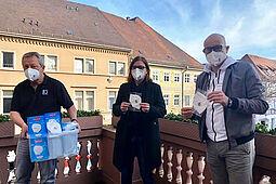 """(v.l.) Gerhard Kessler, Kuratoriumsvorsitzende und Ortsvorsteherin Alexandra Ries, 1. Vorsitzender Roland Laue mit der FFP2-Maske Sonderedition """"Durlacher Engele"""". Foto: pm"""