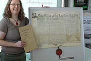 Stadtarchivarin Dr. Katrin Dort zeigt ein Beispiel aus dem 18. Jahrhundert: Bisher wurde die Urkunde im säurehaltigen Papierumschlag gelagert (links), jetzt liegt sie plan im Karton. Fotos: cg