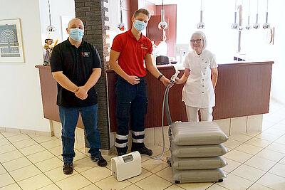 (v.l.) Mike Linsel und Aaron Kunz vom DRK-Kreisverband Karlsruhe bedanken sich bei Dr. Dr. Evelyn Beisel für das Hebekissen. Foto: pm